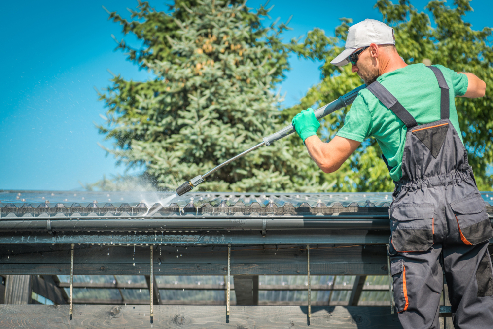 professional cleaning a gutter using pressure washer